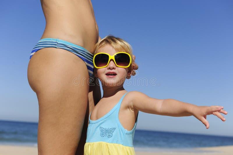 Matriz e filha com os óculos de sol na praia imagens de stock