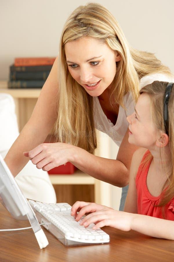 Matriz e filha em casa que usam o computador fotos de stock royalty free