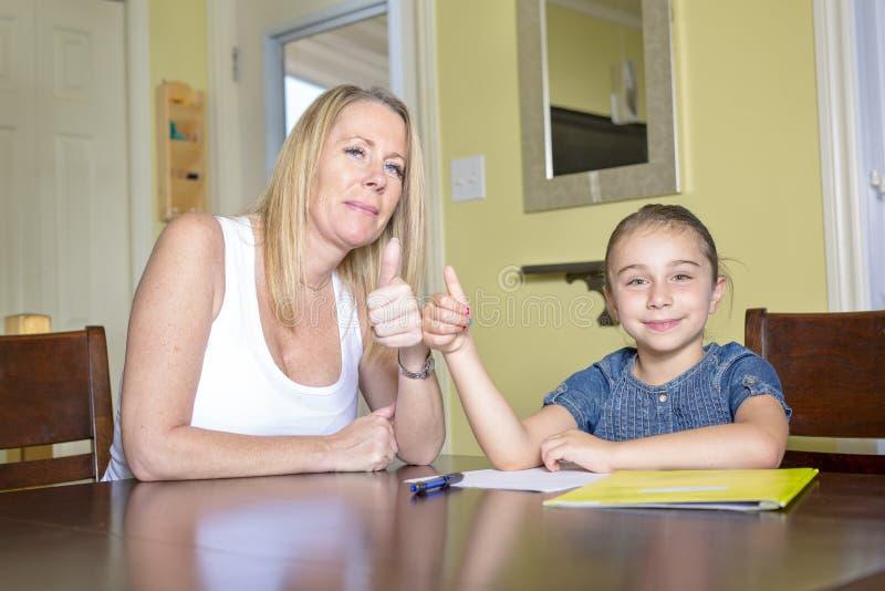 Matriz e filha em casa Trabalhos de casa da menina dos teachs da mamã imagem de stock