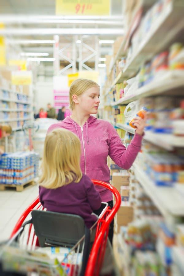 Matriz e filha na seção do comida para bebé na loja foto de stock