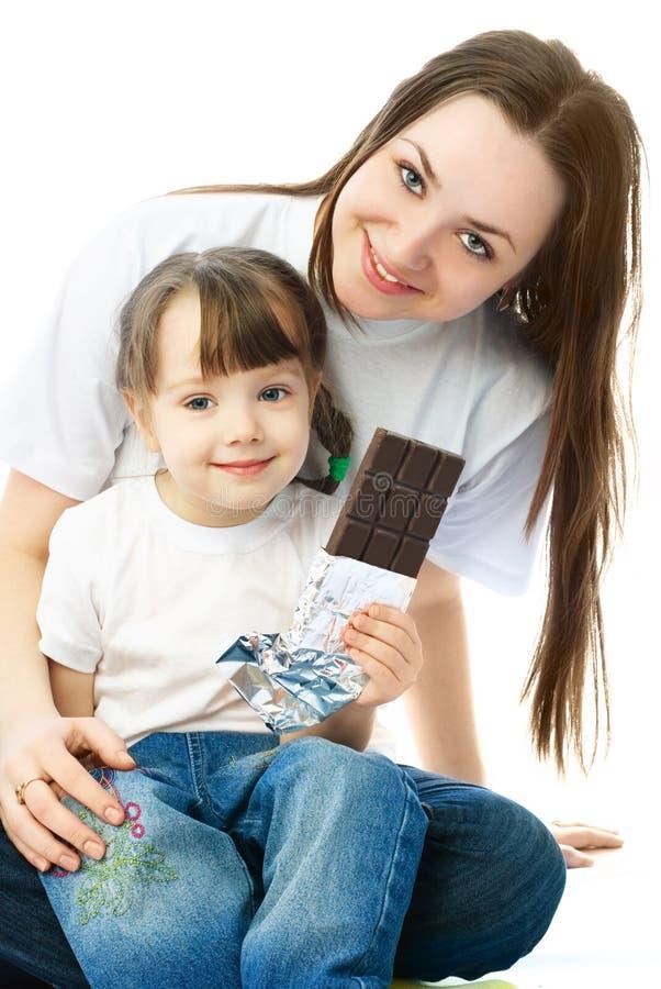 Matriz e filha que comem o chocolate imagem de stock