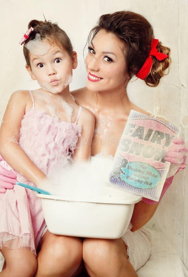 Matriz e filha que fazem a lavanderia fotos de stock