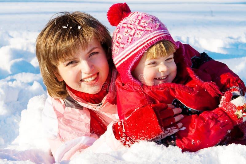 Matriz e filha que jogam na neve imagem de stock