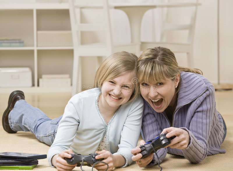 Matriz e filha que jogam o jogo video foto de stock