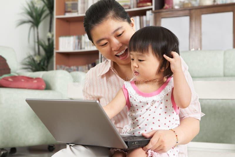 Matriz e filha que jogam o portátil junto imagem de stock