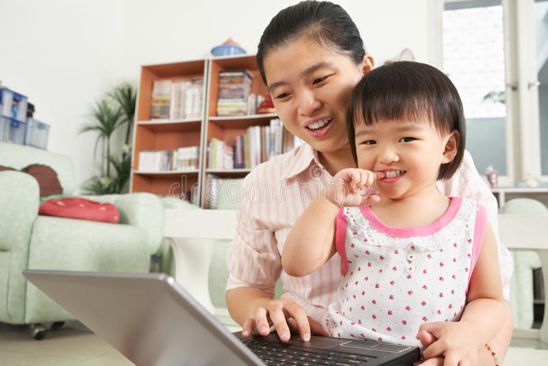 Matriz e filha que jogam o portátil junto imagens de stock