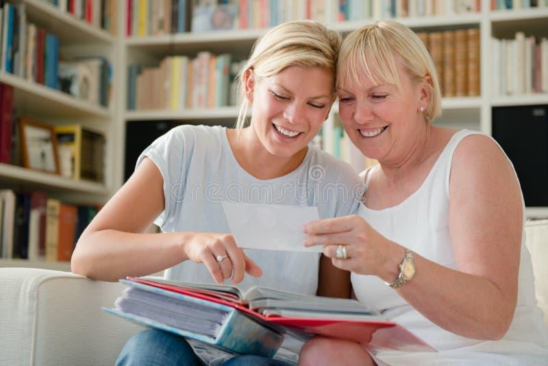 Matriz e filha que olham retratos fotos de stock