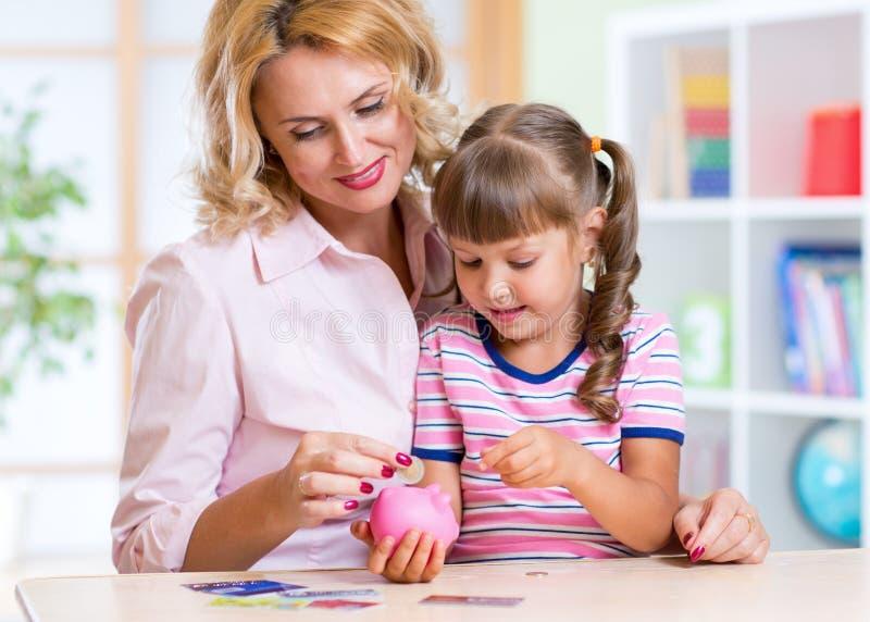 Matriz e filha que põr moedas no banco piggy fotografia de stock
