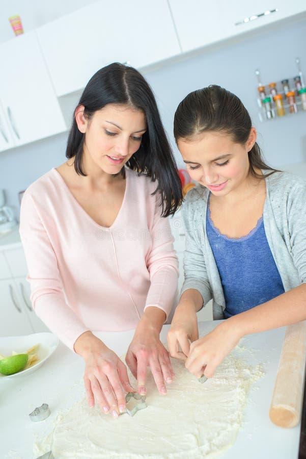 Matriz e filha que preparam o bolo imagem de stock