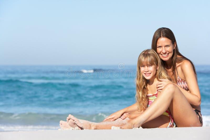 Matriz e filha que relaxam junto na praia fotografia de stock royalty free