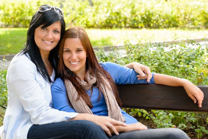 Matriz e filha que relaxam no banco de parque fotos de stock royalty free