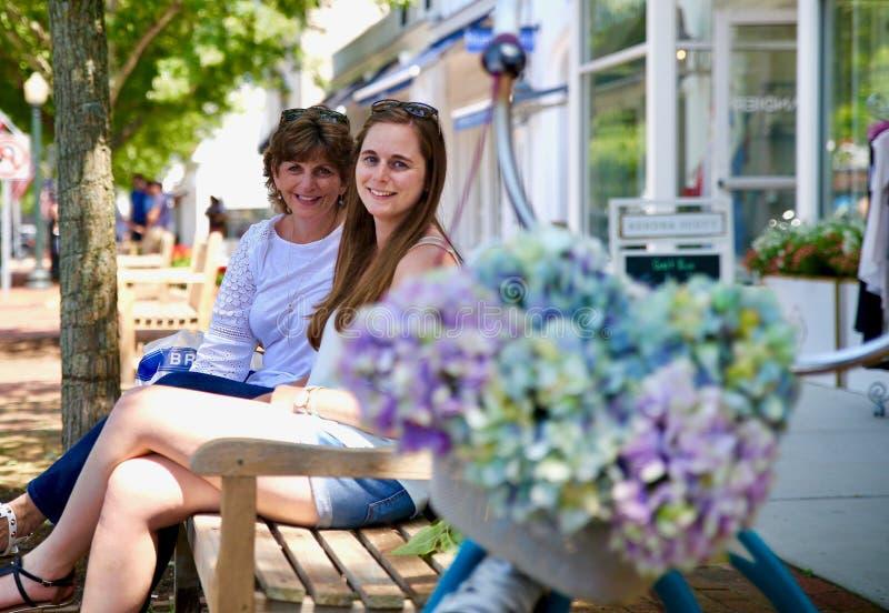 Matriz e filha que sentam-se em um banco fotos de stock royalty free