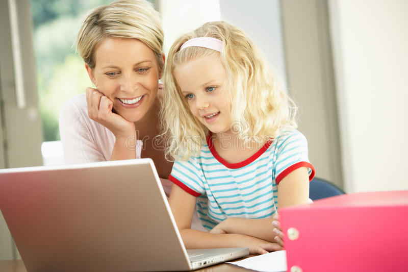 Matriz e filha que usa o portátil em casa fotografia de stock royalty free