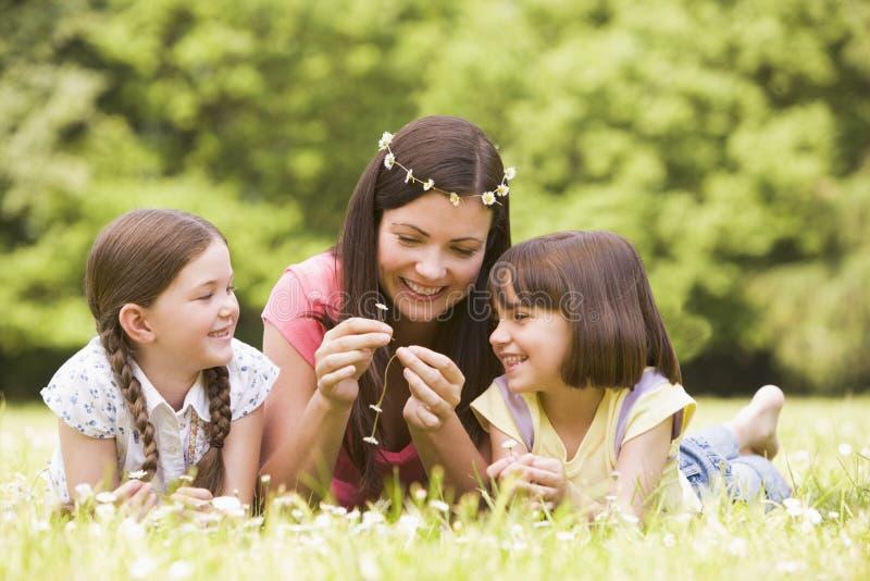 Matriz e filhas que encontram-se ao ar livre com flores fotos de stock