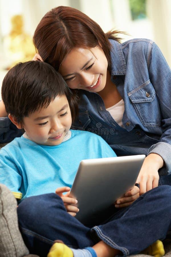 Matriz e filho chineses que usa o computador da tabuleta foto de stock royalty free