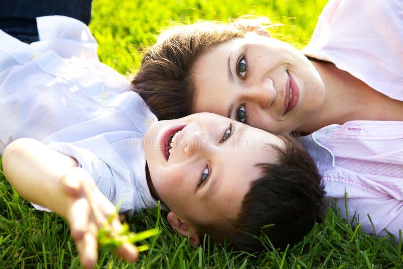 Matriz e filho que encontram-se na grama foto de stock