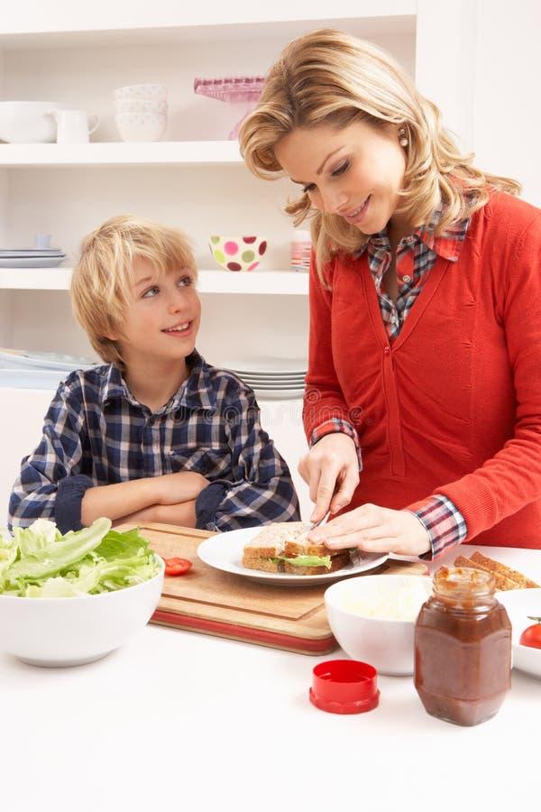 Matriz e filho que fazem o sanduíche na cozinha imagens de stock