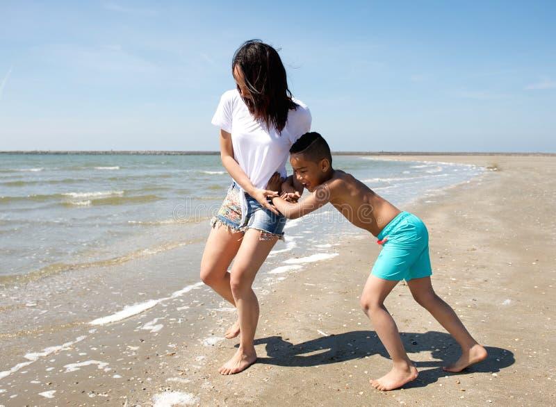 Matriz e filho que jogam na praia foto de stock