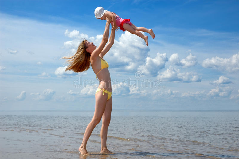 A matriz e o bebê têm o divertimento na praia fotografia de stock