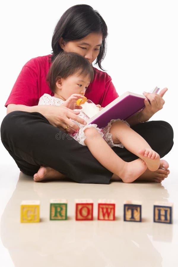 Matriz e seu livro de leitura da menina foto de stock