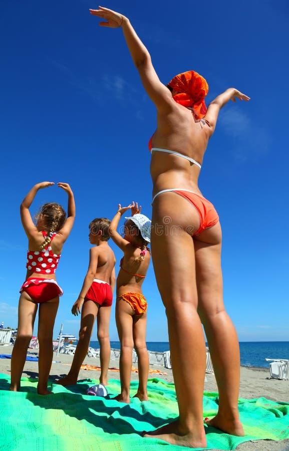 Matriz e suas crianças na praia fotos de stock