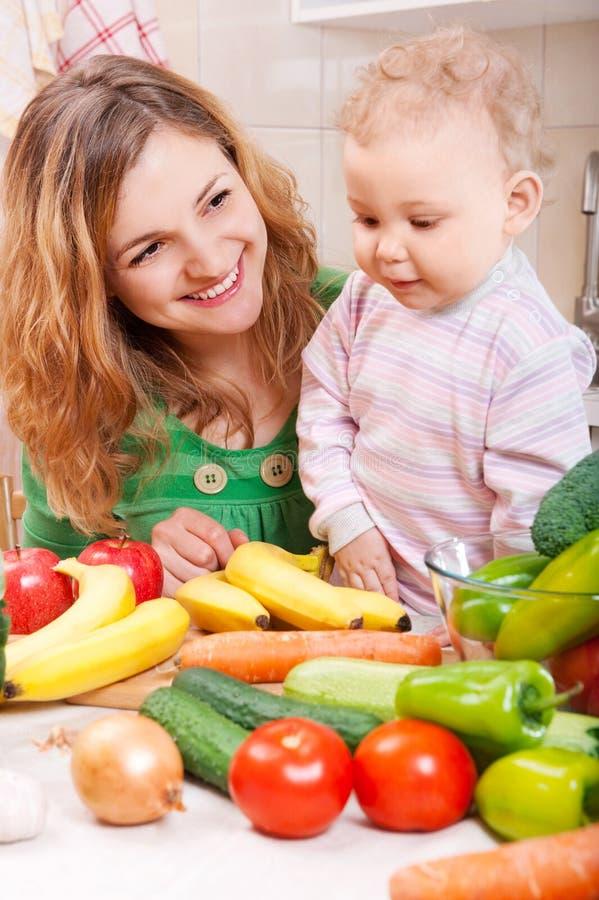 Matriz feliz com a filha do bebê que prepara vegetais imagens de stock
