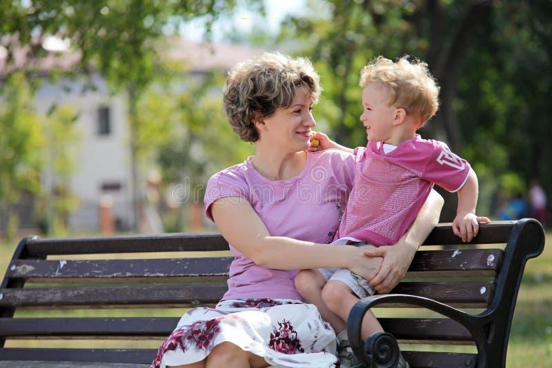 Matriz feliz e filho que sentam-se no banco no parque imagem de stock royalty free