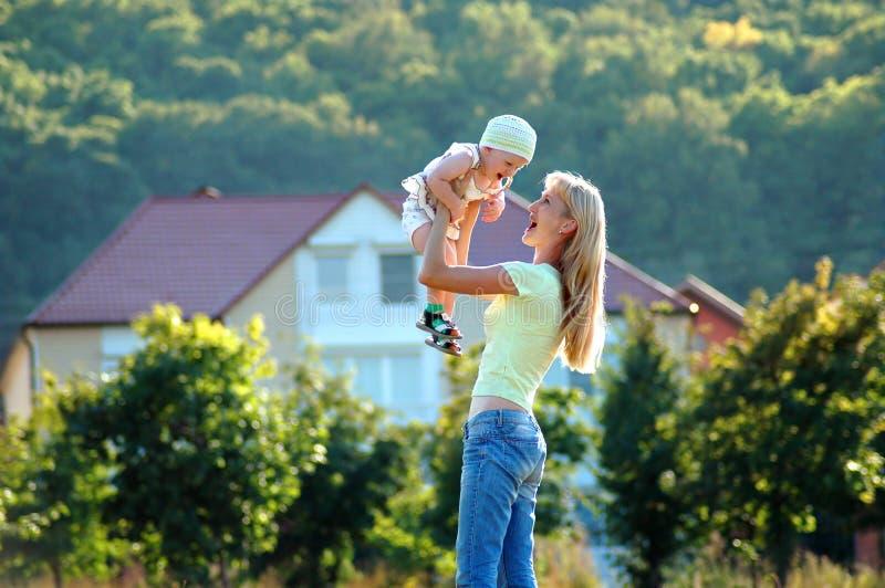 A matriz feliz mantem a criança na mão imagem de stock