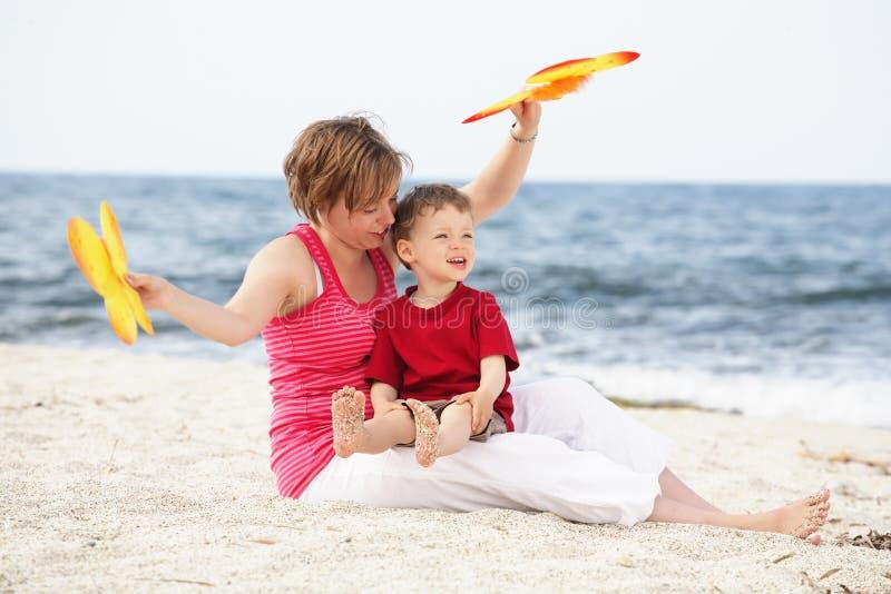 Matriz feliz nova que joga com seu filho no bea fotografia de stock royalty free