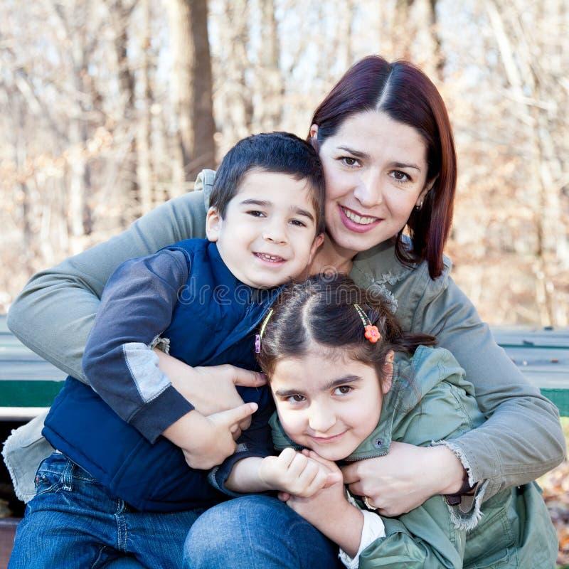 Matriz feliz que abraça suas crianças foto de stock royalty free