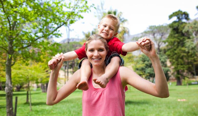 Matriz feliz que dá a seu filho um passeio do sobreposto imagem de stock
