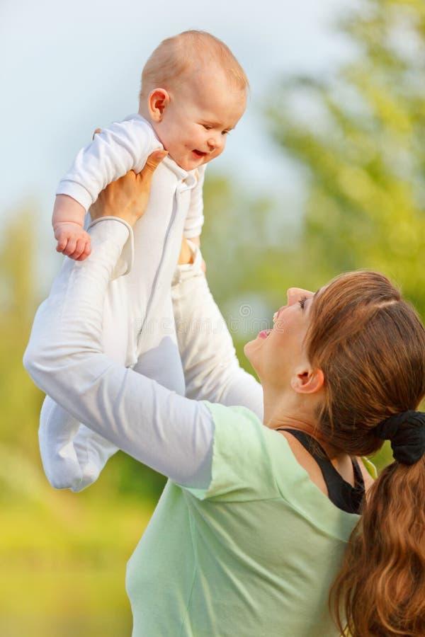 Matriz feliz que joga com o bebê de sorriso no parque imagem de stock