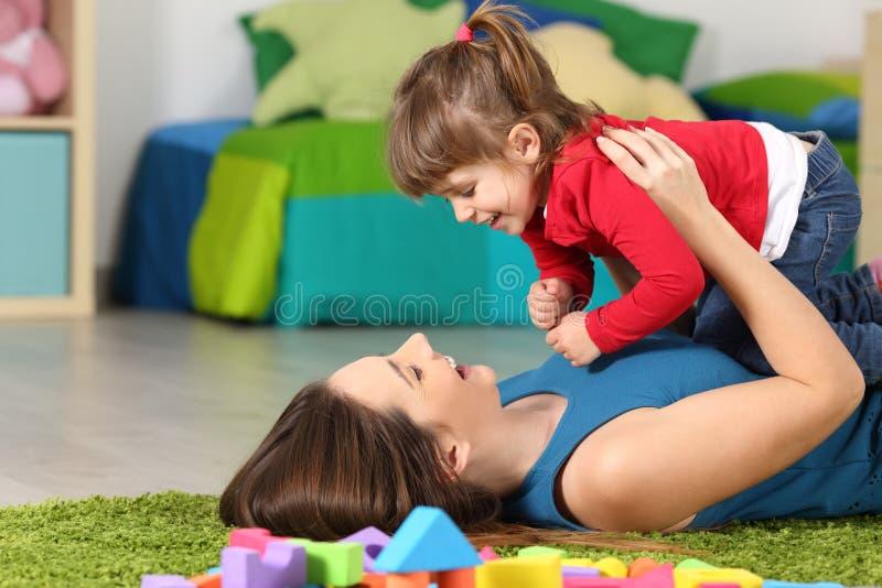 Matriz feliz que joga com sua filha imagem de stock