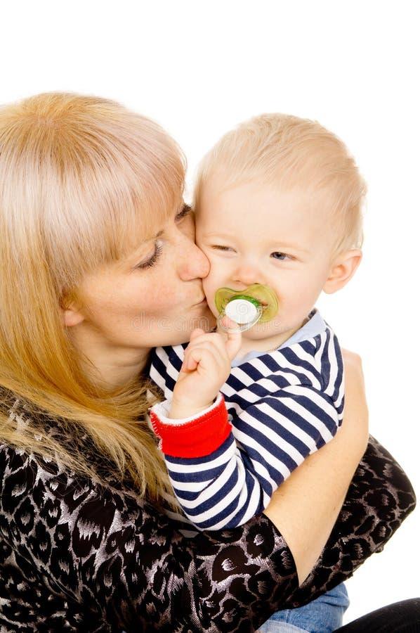 A matriz mantem o bebê pequeno bonito em seus braços, sugando um pacifie imagem de stock