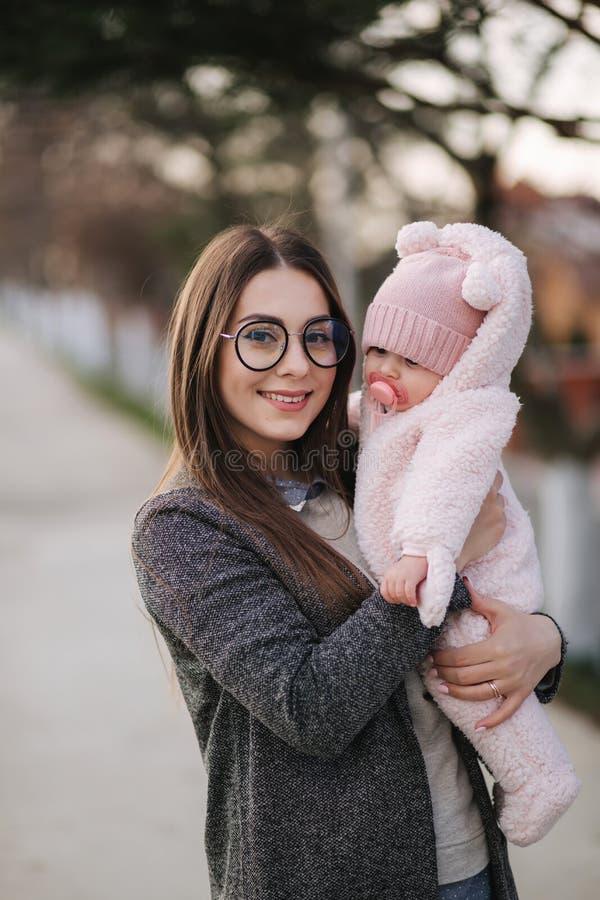 Matriz nova com seu bebê pequeno Bebê da posse da mamã nas mãos Família feliz foto de stock