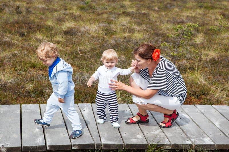 Matriz nova e dois rapazes pequenos no parque natural do verão imagem de stock royalty free