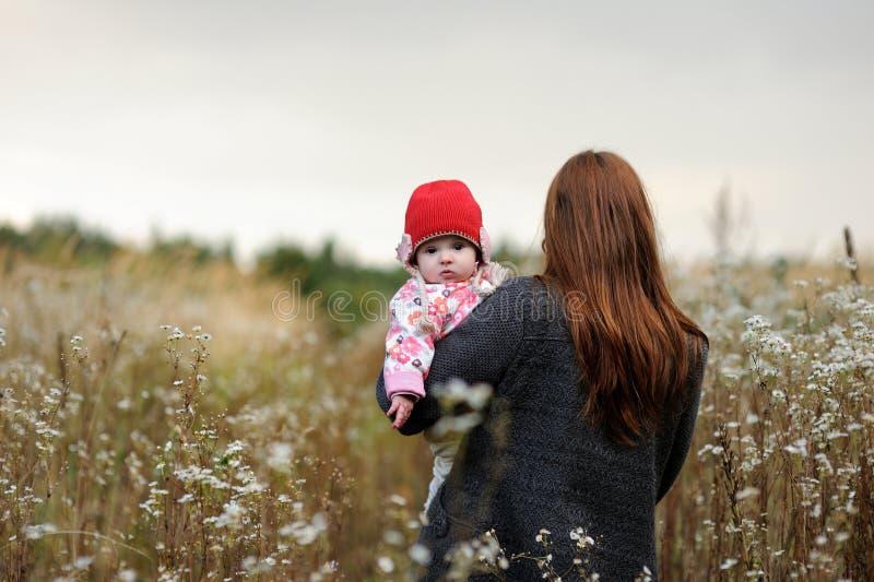 Matriz nova que anda afastado prendendo seu bebê. foto de stock royalty free