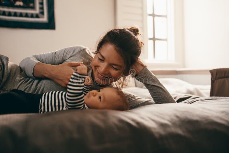 Matriz nova que joga com seu bebê imagem de stock