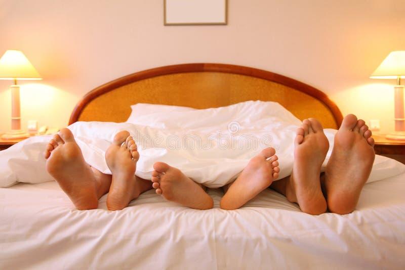 A matriz, o pai e a criança encontram-se na cama fotos de stock