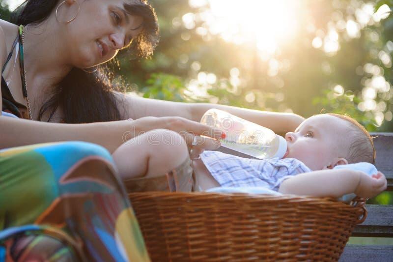 Matriz que alimenta seu bebê no parque imagem de stock royalty free