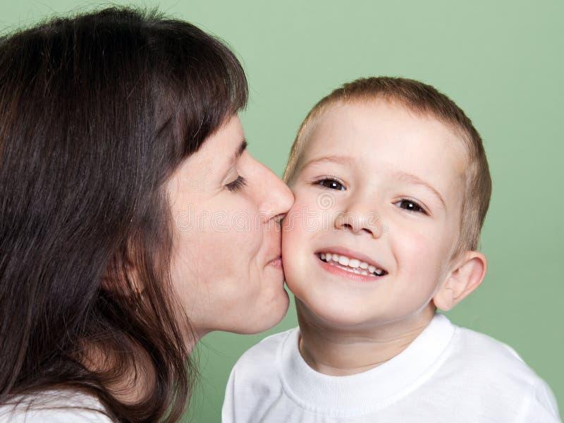 Matriz que beija a criança foto de stock