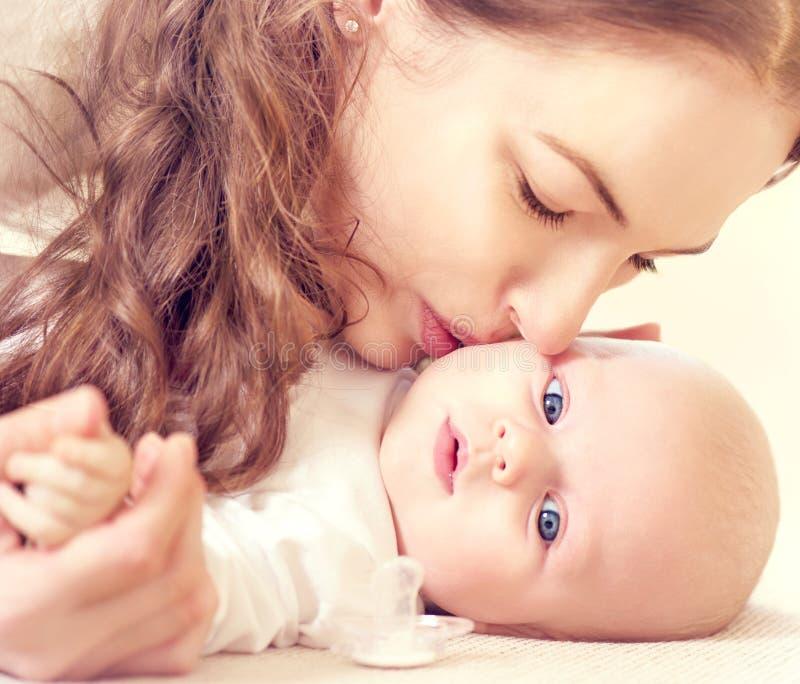 Matriz que beija seu bebê recém-nascido foto de stock