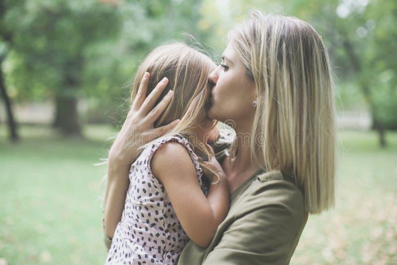 Matriz que beija sua filha pequena imagens de stock royalty free
