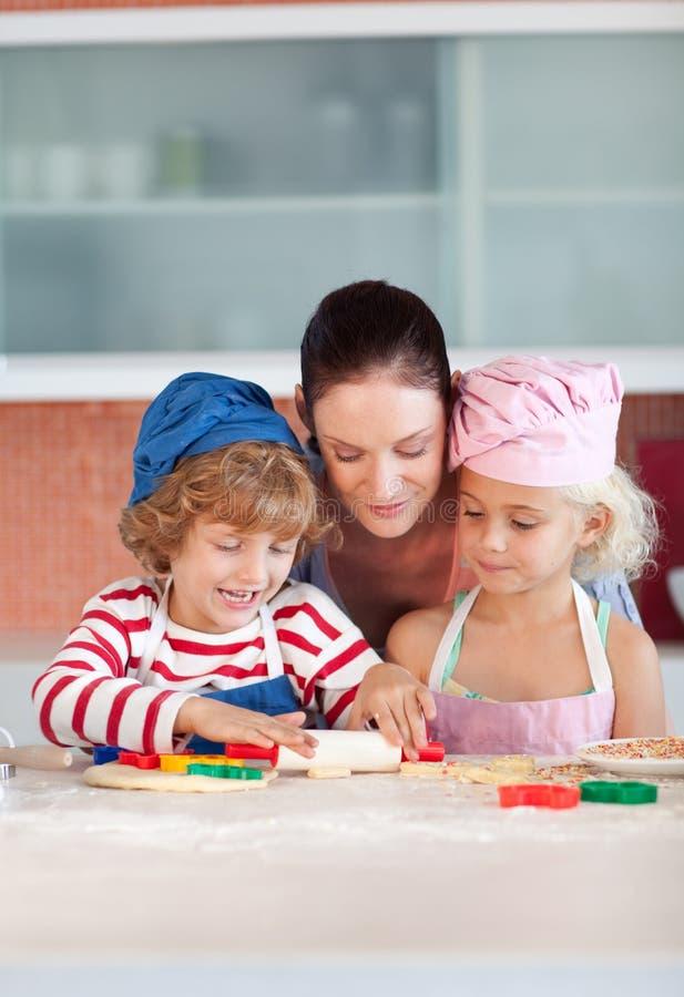 Matriz que interage com as crianças na cozinha imagem de stock royalty free