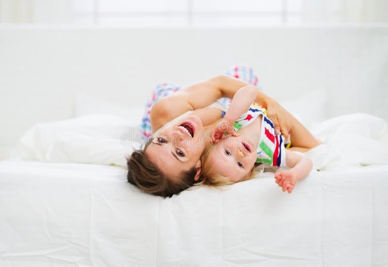 Matriz que joga com o bebê na cama fotos de stock royalty free