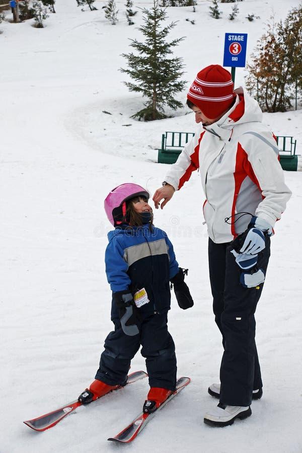 A matriz toma a filha à lição do esqui imagem de stock