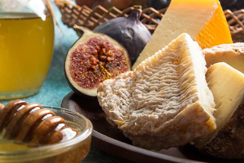 Matsammansättning med stycket av möglig ost, honung, fikonträd royaltyfria bilder