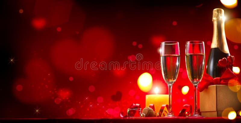 Matställe för romantiker för dag för valentin` s Champagne, stearinljus och gåvaask över röd bakgrund arkivbilder