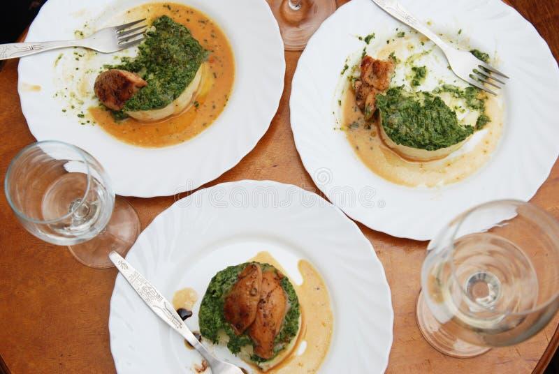 matställe Fegt bröst för stek med spenat och mosade potatisar på den runda tabellen med vitt vin Glasess royaltyfria foton