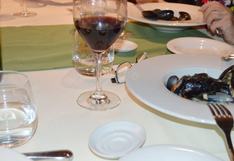 Matställe i en traditionell italiensk restaurang med skaldjur, musslor i en platta och ett exponeringsglas av rött vin royaltyfria foton